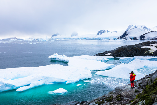 Tourist taking photos of amazing frozen landscape in Antarctica with icebergs, snow, mountains and glaciers, beautiful nature in Antarctic Peninsula with ice 1162427378