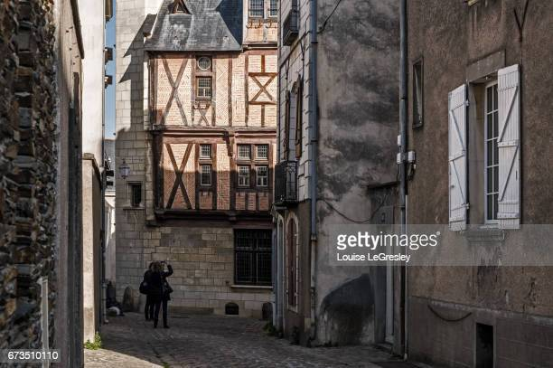 Tourist taking photos of the achitecture in the old town of Angers, France
