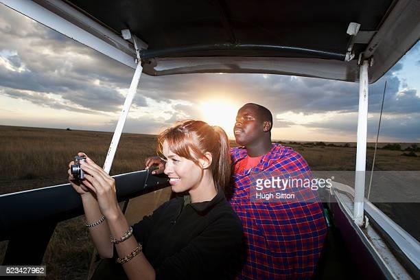 tourist taking picture from vehicle with guide, maasai mara game reserve, kenya - hugh sitton - fotografias e filmes do acervo
