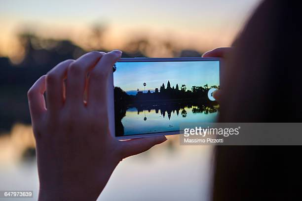 Tourist taking picture of Angkor Wat