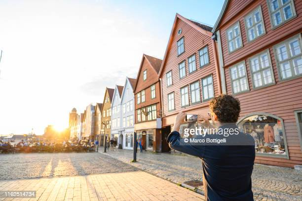 tourist taking picture of bryggen at sunset, bergen, norway - bergen norway stock pictures, royalty-free photos & images