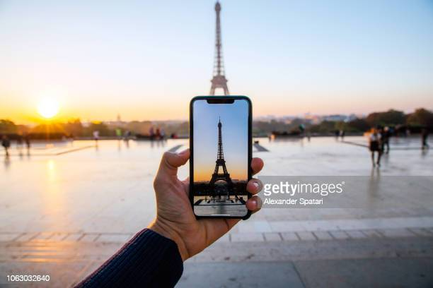 tourist taking picture of eiffel tower with smart phone, personal perspective view, paris, france - reiseziel stock-fotos und bilder