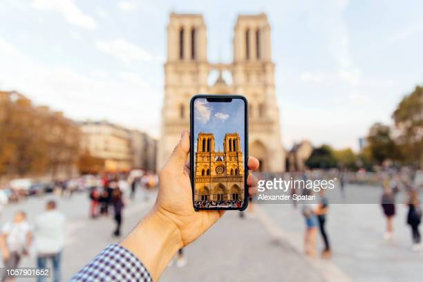 tourist taking picture of notre dame cathedral with smart phone, personal perspective view - al centro foto e immagini stock