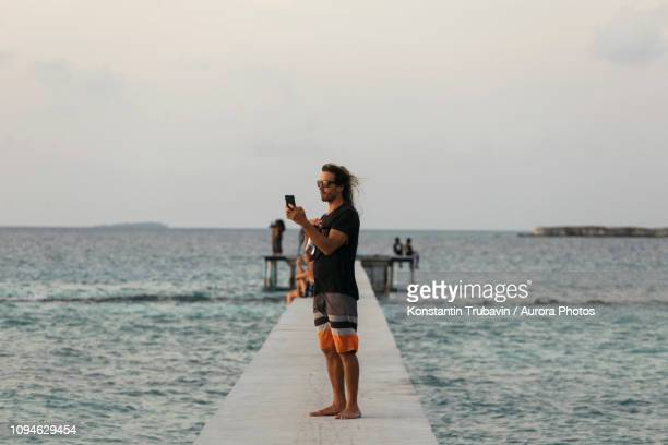 tourist taking picture on pier,thulusdhoo, male, maldives - male maldives stock pictures, royalty-free photos & images