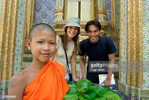 tourist taking picture with young monk, bangkok, thailand - hugh sitton stock pictures, royalty-free photos & images