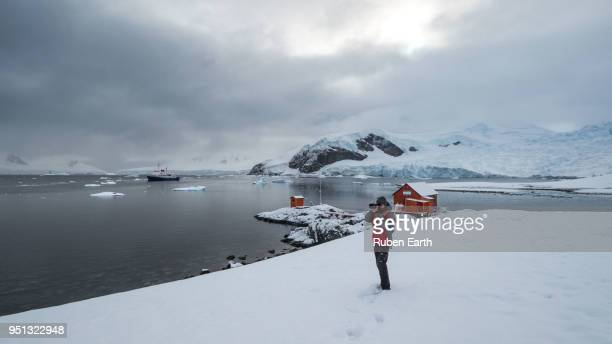 Tourist taking pictures in Paradise bay in the Antarctica Peninsula