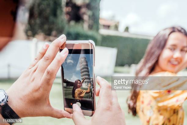 tourist taking pictures  in pisa tower, italy - pisa stock pictures, royalty-free photos & images