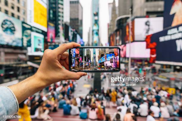 tourist taking pictures of times square, personal perspective view, new york, usa - photographing stock pictures, royalty-free photos & images