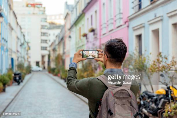 tourist taking pictures with mobile phone on the street, rear view, paris, france - photo messaging stock pictures, royalty-free photos & images