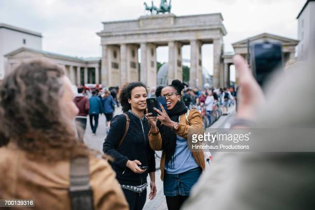 tourist taking selfie at brandenburg gate - central berlin stock photos and pictures
