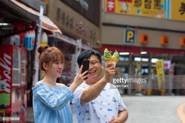 Tourist taking selfie of ice cream cones.