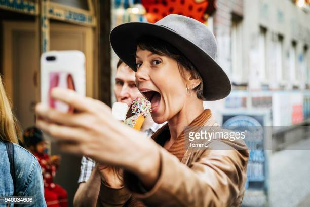 tourist taking selfie while easting an ice cream - city photos stock pictures, royalty-free photos & images
