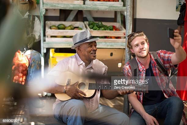 Tourist taking selfie with market trader playing ukulele