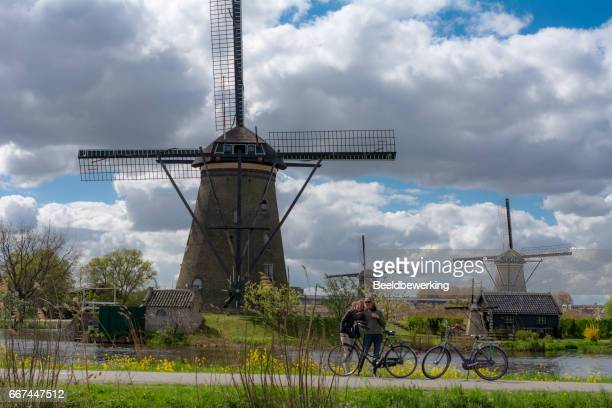 Tourist taking selfies with  the windmills of Kinderdijk