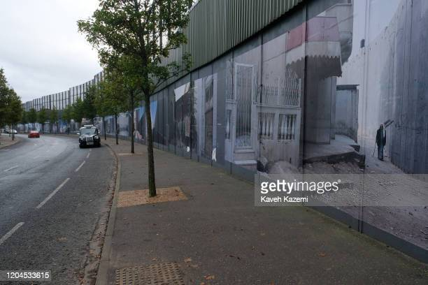 A tourist taxi drives foreign visitors on the Cupar Way which runs between the peace line dividing the Protestant and Catholic communities on October...