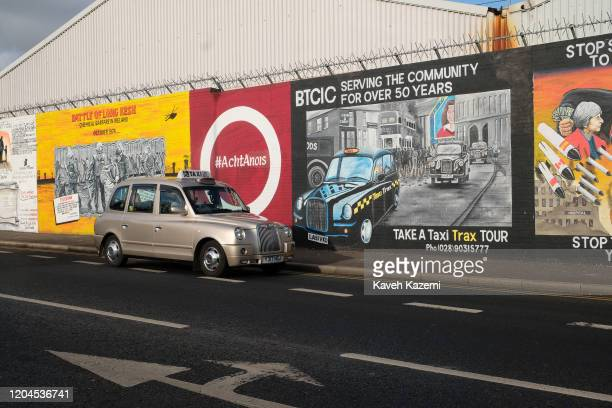 A tourist taxi stops in front of a mural which advertises rental of cabs for foreign visitors eager to see traces of The Troubles on The Falls Road...
