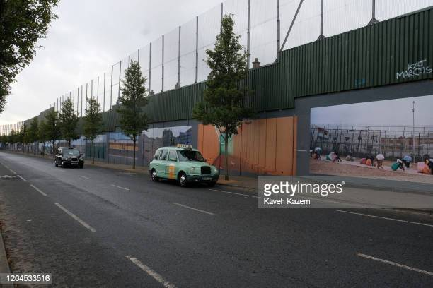 Tourist taxis drive foreign visitors on the Cupar Way which runs between the peace line dividing the Protestant and Catholic communities on October...