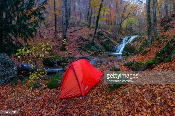 A tourist tent is in the autumn forest. Waterfall and stream on the background. Red foliage is everywhere. Tourist camp. Solo travel.