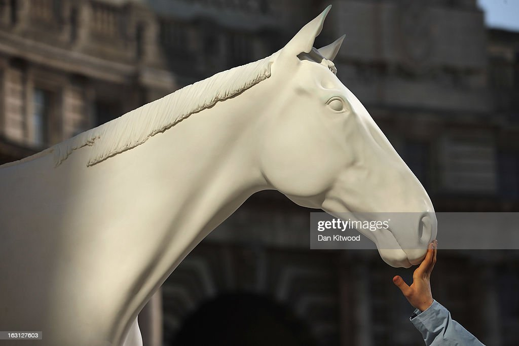 A tourist touches the new sculpture 'The White Horse' by Artist Mark Wallinger after it was unveiled outside the headquarters of The British Council on the Mall on March 5, 2013 in London, England. The British Council unveiled the marble and resin, life-size sculpture representing a thoroughbred racehorse, as it announced a GBP 7 million investment in work connecting UK-based creative talent overseas.