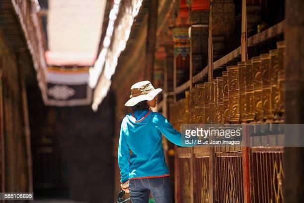 Tourist touching prayer wheel in Jokhang Temple