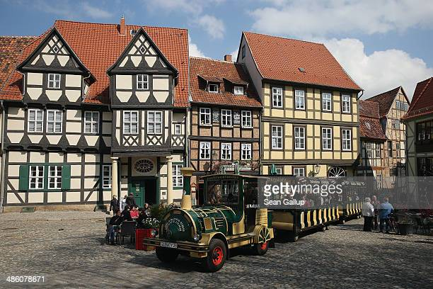 A tourist train makes its way past halftimbered houses on April 20 2014 in Quedlinburg Germany Quedlinburg located in the Harz region dates its...