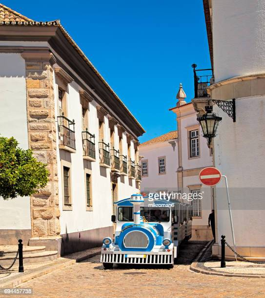 tourist train passing narrow streets of old faro town on hot summer day. - faro city portugal stock photos and pictures