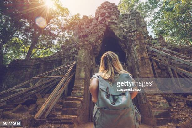 tourist traveling female stands in front of temple complex gate looking up at the sculpture on top, people discovery exploration concept - angkor wat stock pictures, royalty-free photos & images