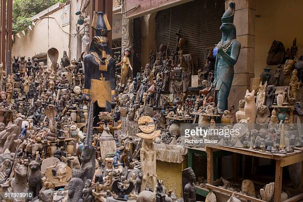 Tourist trinkets and statues in the souk at Luxor Nile Valley Egypt A vast selection of Pharaonic statuettes and figurines are piled up on tables and...