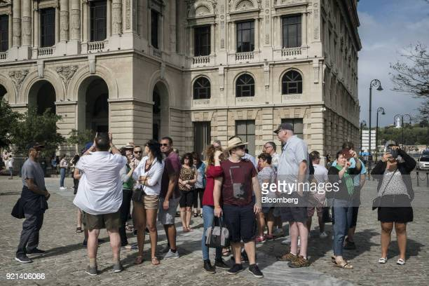 Tourist use mobile devices to take photograph after disembarking an international cruise ship near the port in Havana Cuba on Saturday Jan 27 2018...