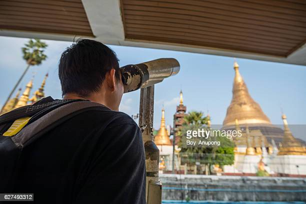 Tourist use the binoculars for looking the diamond and precious gem on the top of Shwedagon pagoda.