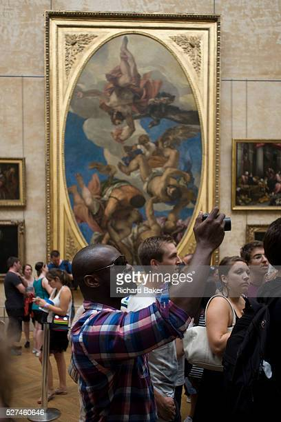 Tourist uses a digital camera to record the Mona Lisa in the Louvre Paris The Mus��e du Louvre is one of the world's largest museums the most visited...