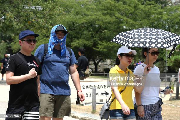 A tourist uses a handkerchief to cover his head from sunlight as the city temperature reaches 36 degrees celsius on July 25 2018 in Himeji Japan A...