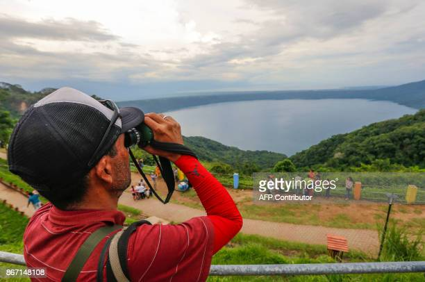 A tourist uses a pair of binoculars to watch at the Laguna de Apoyo volcanic lagoon from Catarina viewpoint in Masaya about 40 kilometres from...