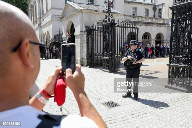 A tourist uses a smartphone to take a picture of an armed police officer at Horse Guards Parade the day after a terror attack in London UK on Sunday...