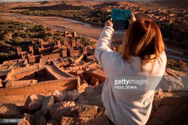 A tourist uses her phone to photograph the Kasbah of AitBenHaddou where scenes depicting the fictional city of Yunkai from the hit HBO television...