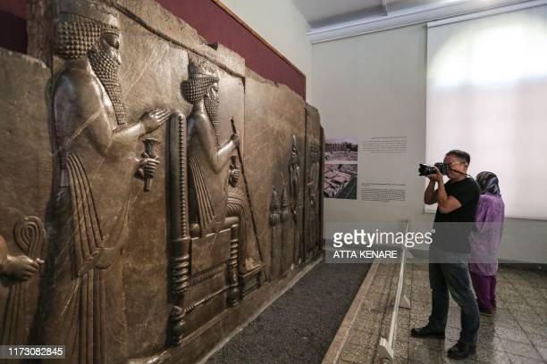 Tourist uses his camera to take a picture of the Persepolis relief depicting a historical scene and king Darius while visiting Iran's National Museum...