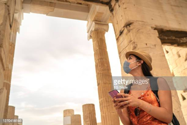 tourist using face mask and using smartphone visiting ancient greek city - greece stock pictures, royalty-free photos & images