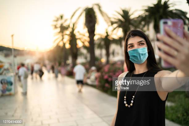 tourist using face mask taking a selfie during vacations in greece - greece tourism stock pictures, royalty-free photos & images