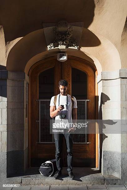 Tourist using smart phone while standing at doorway