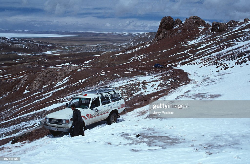 A tourist vehicle is stuck in a snowdrift that blew in overnight on a 5000-meter pass, blocking the road. The road was eventually dug out by hand..