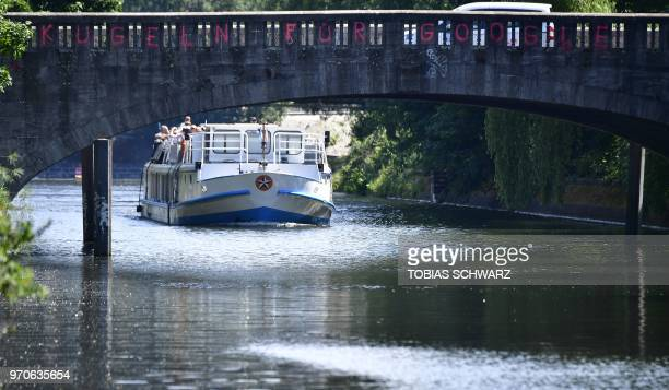 A tourist vessel passes a bridge showing a graffiti reading 'Bullet for Google' in Berlin's Kreuzberg district on May 22 2018 Global cities from...