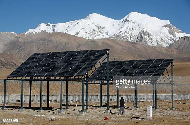 A tourist views solar panels built along the QinghaiTibet railway on December 7 2008 in Damxung County of Tibet Autonomous Region China The 1956km...