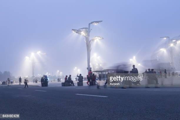 beijing, сhina - october 14, 2016: tourist visit beijing bird nest stadium square at night with lights on under haze pollution. - stadio olimpico nazionale foto e immagini stock
