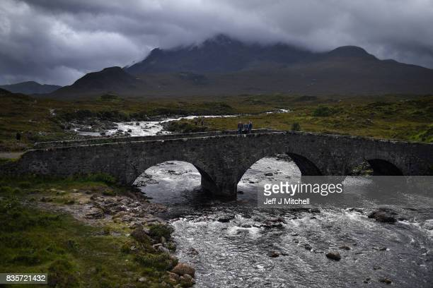 Tourist visit Sligachan Old Bridge on the Isle of Skye on August 17 2017 in Valtos Scotland The Isle of Skye is known as one of the most beautiful...