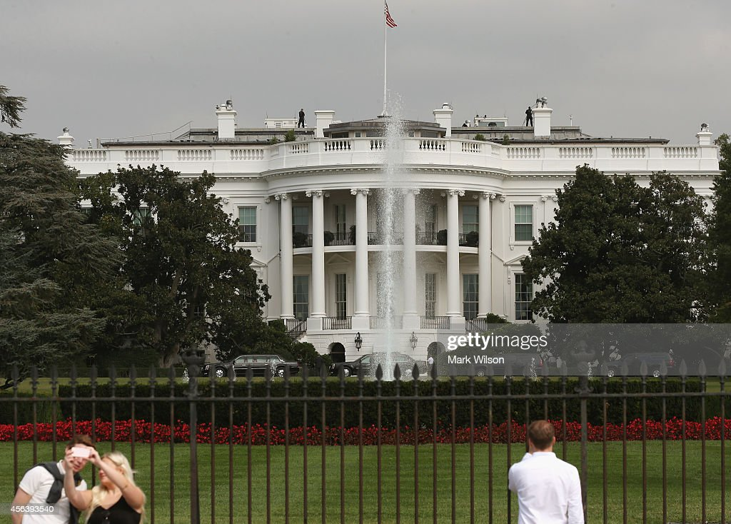 Tourist visit the south side of the White House as members of the US Secret Service stand guard on the roof September 30, 2014 in Washington, DC. White House intruder Omar Gonzalez, the man arrested last week after jumping the White House fence, went deeper into the building than what was previously reported.