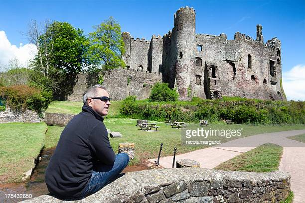 Tourist visiting an old castle ruin, Carmarthenshire, Wales.