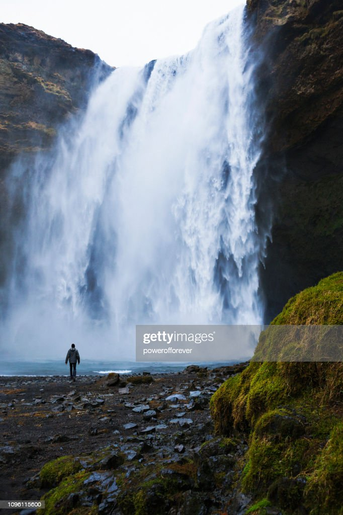 Tourist Visiting Skógafoss Waterfall at Skógar in Iceland : Stock Photo