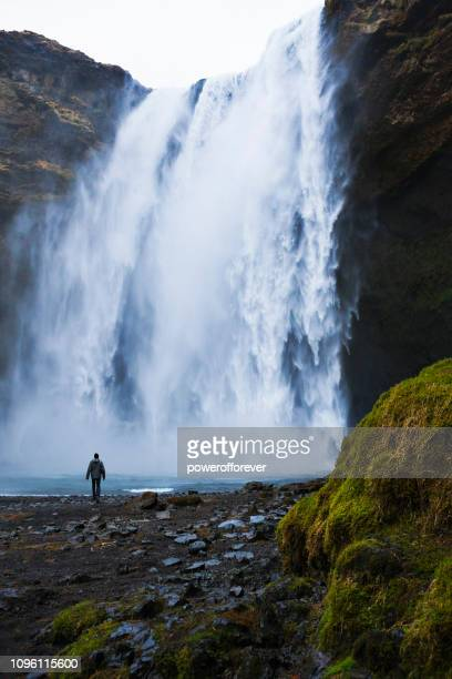 Tourist Visiting Skógafoss Waterfall at Skógar in Iceland