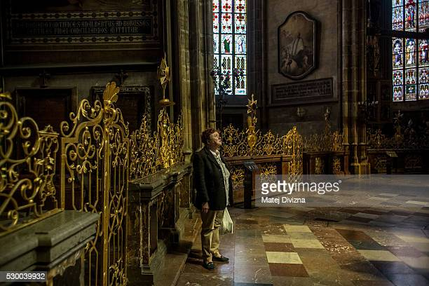 A tourist visits the St Vitus Cathedral on May 9 2016 in Prague Czech Republic Ruler Charles IV began the construction of the St Vitus Cathedral in...