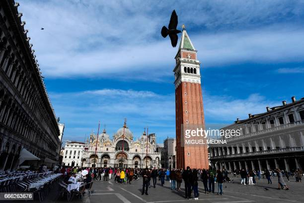 Tourist walk across the Piazza San Marco with the Saint Mark's Basilica and the San Marco Campanile in Venice on April 7 2017 / AFP PHOTO / MIGUEL...